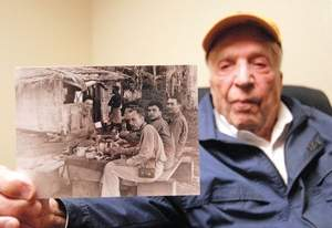 Daily file photo/Mark FoxBill Hirsch holds a photo from his days in World War II in the early 1940s. Hirsch is in the middle on the right side or as he put it 'The good-looking one.'
