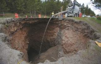 Vail Daily/Dominique TaylorWork crews pour flow fill, a mixture of cement, soil and water, into a sinkhole estimated at 35 feet by 35 feet across and 100 feet deep to fill it up Wednesday on U.S. Highway 24 near Tennessee Pass. Colorado Department of Transportation officials estimate the highway will be closed to through traffic until early August.