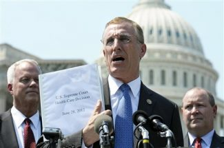 FILE - In this Thursday, June 28, 2012 file photo, Rep. Tim Murphy, R-Pa., center, holds up a copy of the Supreme Court's health care ruling during a news conference by the GOP Doctors Caucus on Capitol Hill in Washington. Republicans in at least three states want to abandon an expansion of Medicaid in President Barack Obama's health care overhaul, and more than a dozen other states are considering it in the wake of the June 28, 2012 Supreme Court decision removing the threat of federal penalties. The states considering whether to withdraw from the expansion include presidential battlegrounds Florida, Ohio, Pennsylvania and Colorado. (AP Photo/Cliff Owen)