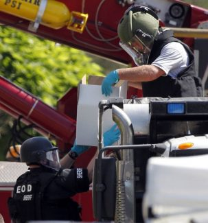 """Explosives from the apartment of alleged gunman James Holmes are loaded with sand into a dump truck for disposal Saturday, July 21, 2012 in Aurora, Colo. Authorities reported that 12 died and more than three dozen people were shot during an assault at a movie theatre midnight premiere of """"The Dark Knight Rises."""" (AP Photo/Alex Brandon)"""