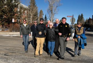 Summit Daily/Mark FoxFlorence Birge is escorted across the street in January during the 'Good Deed Day' by Sheriff John Minor and his posse.