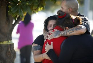 Three women and a man, who did not speak to the media, hug together outside the police perimeter in central Fresno where a shooting occurred at a workplace Tuesday, Nov. 6, 2012. A parolee who worked at a California chicken processing plant opened fire at the business on Tuesday, killing one person and wounding three others, before shooting himself, police said. (AP Photo/The Fresno Bee, Craig Kohlruss)  LOCAL PRINT OUT; LOCAL TV OUT