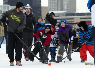 Los Angeles King's Mike Richards, left, and Winnipeg Jets' Andrew Ladd, rear left, play street hockey with hockey fans and a few fellow NHL players atop a parking garage at the Forks in Winnipeg, Manitoba, Tuesday, Nov. 13, 2012. (AP Photo/The Canadian Press, David Lipnowski)