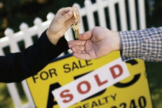Woman handing man keys in front of house sold sign