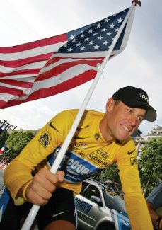 "FILE - In this July 24, 2005 file photo, Lance Armstrong, of Austin, Texas, carries the United States flag during a victory parade on the Champs Elysees avenue in Paris, after winning his seventh straight Tour de France cycling race. In 2012, Armstrong decided to give up the battle against doping charges, saying ""enough is enough"" but acknowledging no wrongdoing. The move began his swift fall from being perhaps the nation's best-known cancer-fighting hero, and though he maintains he was victimized by a ""witch hunt"" he was still stripped of all seven of his Tour de France victories. (AP Photo/Peter Dejong, File)"