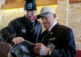 """Professional skier, Chris Anthony, left, shows 10th Mountain Division World War II veteran, Earl Clark the story in Mile High Sports magazine about the new Warren Miller film, """"Climb To Glory:Legacy of the 10th Mountain Ski Troopers"""" that Anthony is Thursday, Jan. 3, 2013 in Vail, Colo. (AP Photo/Vail Daily, Dominique Taylor)"""