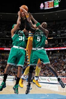 Boston Celtics forwards Paul Pierce, left, and Kevin Garnett, right, box out Denver Nuggets forward JaVale McGee for a rebound during the fourth quarter of the Nuggets' 97-90 victory in an NBA basketball game in Denver on Tuesday, Feb. 19, 2013. (AP Photo/David Zalubowski)