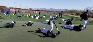 Colorado Rockies pitchers and catchers stretch before a spring training baseball workout Tuesday, Feb. 12, 2013, in Scottsdale, Ariz. (AP Photo/Darron Cummings)