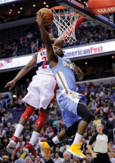 Denver Nuggets point guard Ty Lawson, right, goes to the basket against Washington Wizards guard John Wall (2) during the first half of an NBA basketball game, Friday, Feb. 22, 2013, in Washington. (AP Photo/Nick Wass)