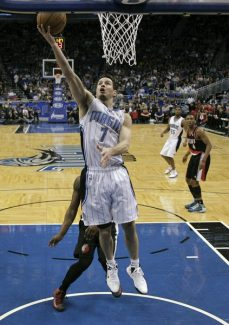 Orlando Magic's J.J. Redick (7) drives to the basket and makes a shot in front of Portland Trail Blazers' Wesley Matthews during the first half of an NBA basketball game, Sunday, Feb. 10, 2013, in Orlando, Fla. (AP Photo/John Raoux)