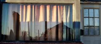 Buildings at the EVRAZ Pueblo steel mill are reflected in the window of a building near the former Colorado Fuel and Iron plant on the southern end of Pueblo. In the 1960s, CF&I was the economic engine and racial equalizer for Colorado's southernmost major city. By the early 1980s, manufacturing operations in Pueblo and across the United States were hit by stiff international competition that led to drastic cutbacks and factory closures. The downturn in manufacturing hurt minority workers disproportionately in Colorado and across the U.S. (Joe Mahoney/The iNews Network)