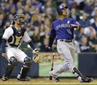 Colorado Rockies' Carlos Gonzalez( 5) and Milwaukee Brewers catcher Jonathan Lucroy, left, watch Gonzalez's home run in the fifth inning of an Opening Day baseball game Monday, April 1, 2013, in Milwaukee. (AP Photo/Jeffrey Phelps)