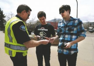 CU 420_003.JPG Boulder Police officer Bud Kelt checks the I.D.'s of University of Colorado seniors Keegan Hebert, center, and Brennan Caley as they walk on to the CU campus on Saturday, April 20. For more photos and video of the 4/20 rally go to www.dailycamera.com