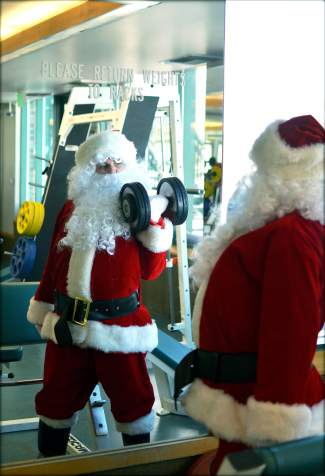 Looking good in red: Santa takes care of his glamour muscles with bicep curls in the weight room at the Breckenridge Recreation Center. Mrs. Claus is an arms girl.