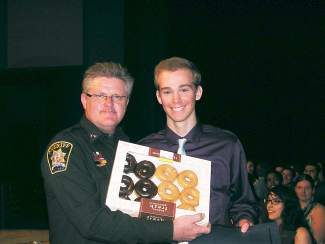 In the spirit of a burgeoning tradition, and having fun at one's own expense, Summit County Sheriff John Minor, left, presented on Monday, April 7 Dillon resident Micah Svenson with a dozen donuts during Summit High School's local scholarship presentations. In addition to the donuts, Svenson received the sheriff's office's annual Citizenship Award Scholarship.