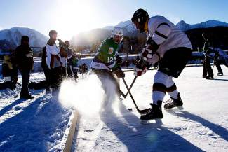 Players in the men's division go for the puck during the 2015 Pabst Colorado Pond Hockey Tournament at North Pond Park in Silverthorne. The tourney returns to North Pond this weekend with 150 teams from 45 states and several countries.