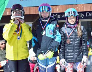 Loveland Ski Club slalom racer Dasha Romanov (right) on the podium after taking third at the Can Am finals in Maine on March 26. Podium (left to right): Chloe Lathrop in second, CJ LaDue in first, Dasha Romanov in third.