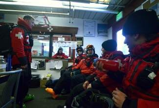Ski patrollers talk in the Keystone patrol headquarters at the top of Dercum mountain before starting afternoon sweep. During the winter, a crew of 22 patrollers leaves PHQ at 4 p.m. after checking the backside mountains to check for guests and rope off trails.