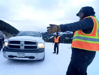 Loveland Ski Area veteran Brett Butson guides a truck into the parking lot early on opening day. For 10 years, Butson has set aside day-to-day work as base operations manager to park cars on the first day of the season.