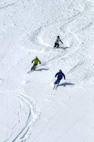 A Breckenridge ski instructor leads two students through powder during an adult lesson. The resort's expert terrain at Peak 6 is a good place for fine-tuning backcountry techniques before heading out of bounds.