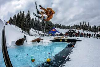 A skier in full regalia gets inverted over the pool at the 2016 Red Bull SlopeSoakers rail jam in Copper on April 17.