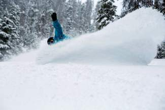 Slash: A snowboarder lays out a gorgeous powder spray at Keystone early on Tuesday morning. The resort recorded 14 inches before lifts opened, followed by Arapahoe Basin with 10 inches, Breckenridge with 9 inches and Copper with 7 inches.