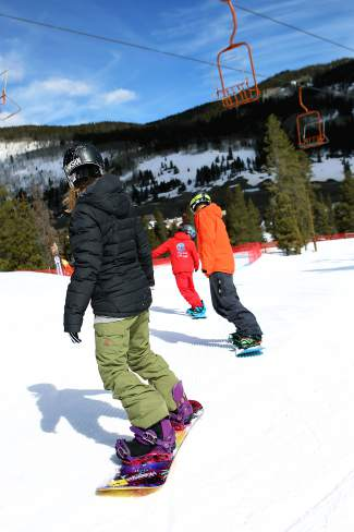 A Copper snowboard instructor leads two students through turning drills on mellow terrain just above West Village. Instructors and coaches recommend practicing advanced techniques on flat terrain before moving to the mountain.