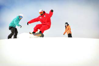 A snowboard instructor takes an advanced class on a playful warm-up run at Copper Mountain. Like skiing, snowboard instructors suggest riding with new (and better) snowboarders to continue progressing.