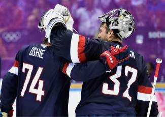United States forward T.J. Oshie (74)  congratulates United States goalie Jonathan Quick (37) after defeating Russia 3-2 in a shootout in a men's ice hockey game at the 2014 Winter Olympics, Saturday, Feb. 15, 2014, in Sochi, Russia.  (AP Photo/The Canadian Press, Nathan Denette)