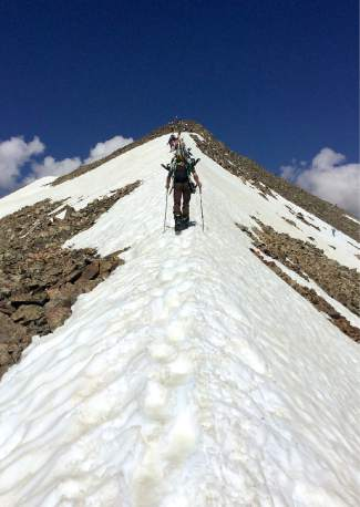 The final ridgeline approach to the summit of Peak 10 for July snowboarding at Fourth of July Bowl.