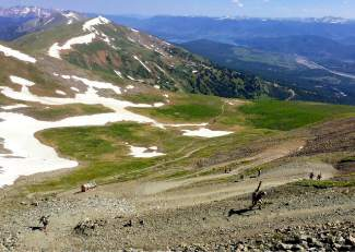 View from The Patch: Skiers and snowboarders pick their way up the switchbacks leading to the summit of Peak 10 and the pockmarked snow at Fourth of July Bowl.