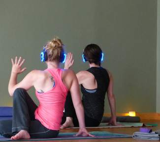 Think of it as cosmic yoga: Two yogis hold a pose at Peak Yoga studio in Dillon on May 29 during an introduction to Sound Off Yoga. The festival-friendly style features noise-cancelling headphones, meditative poses and, of course, eye-catching neon.