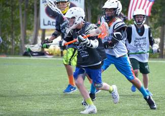 Going for goal: A player weaves past defenders at the Summit Scramble Lacrosse Tournament, hosted by Summit Stix Lacross in Breckenridge Sept. 5-6.
