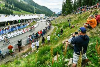 Spectators snap photos as the first group of riders power to the finish line for Stage 2 of the 2015 USA Pro Challenge at Arapahoe Basin.