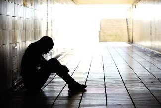Teenager depressed sitting inside a dirty tunnel