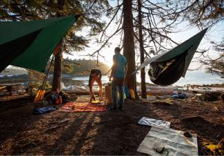 The Hennessy Expedition Asym hammock at a kayaking campsite. The hammock is made for backcountr expeditions, along with other 2016 summer gear like the new Osprey Manta reservoir backpack and waterproof charging station from myCharge.