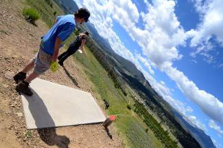 Jessica Leach and Robbie Forbes, both of Summit Cove, eye the basket on Hole 8 of the Lake Dillon Disc Golf Course. The 533-foot hole is one of the hardest on the course, with a steep elevation drop over thick sagebrush.