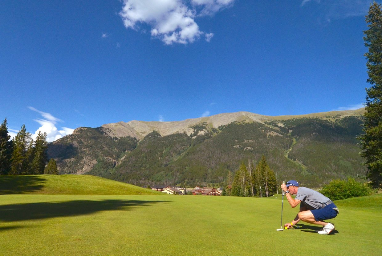 Charlie Levin lines up his putt on the Hole 1 green at Copper Mountain, with views of the Sky Chutes on the Tenmile Range in the background. The course is surrounded by ski lifts, ski runs and the namesake creek, plus several standing water hazards.