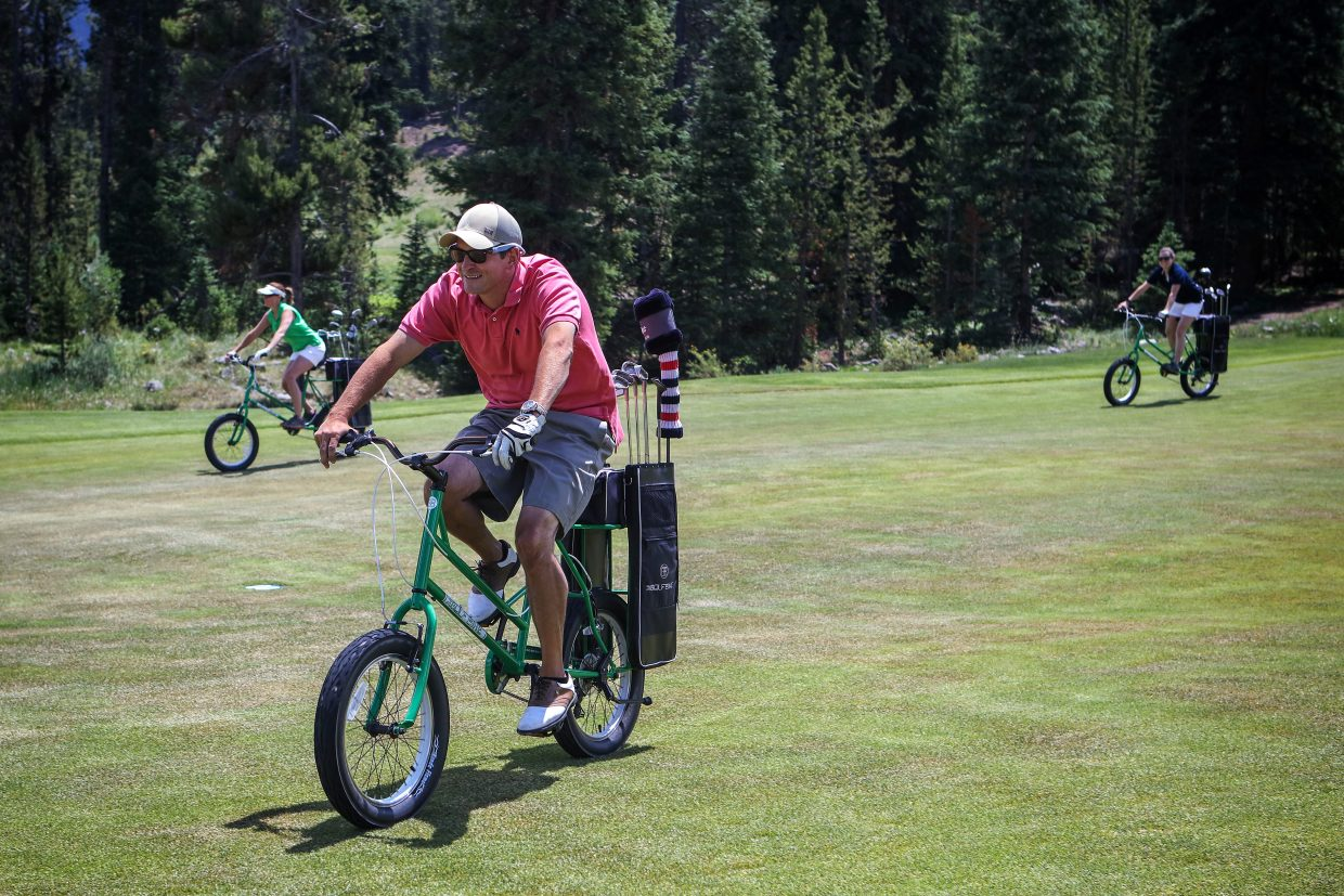 Golfers ride special-made golf bikes at Copper Creek Golf Course. The bikes are new to the course this year and available in place of golf carts.