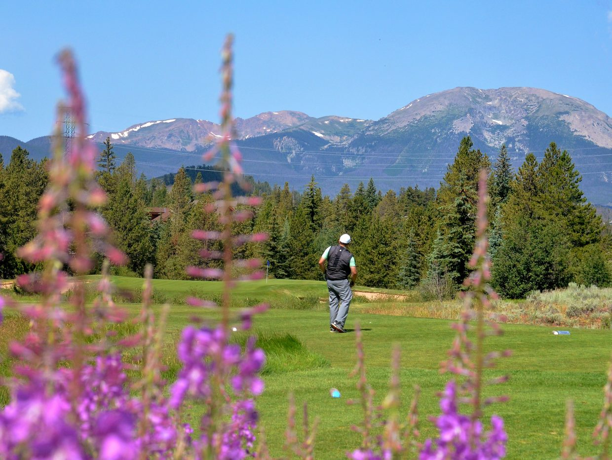 Keystone assistant golf pro Denny Weber watches his shot on Hole 7 at The River Course, with views of Buffalo Mountain in the distance. It's the signature hole on The River Course, one of two full 18s just east of the ski slopes.