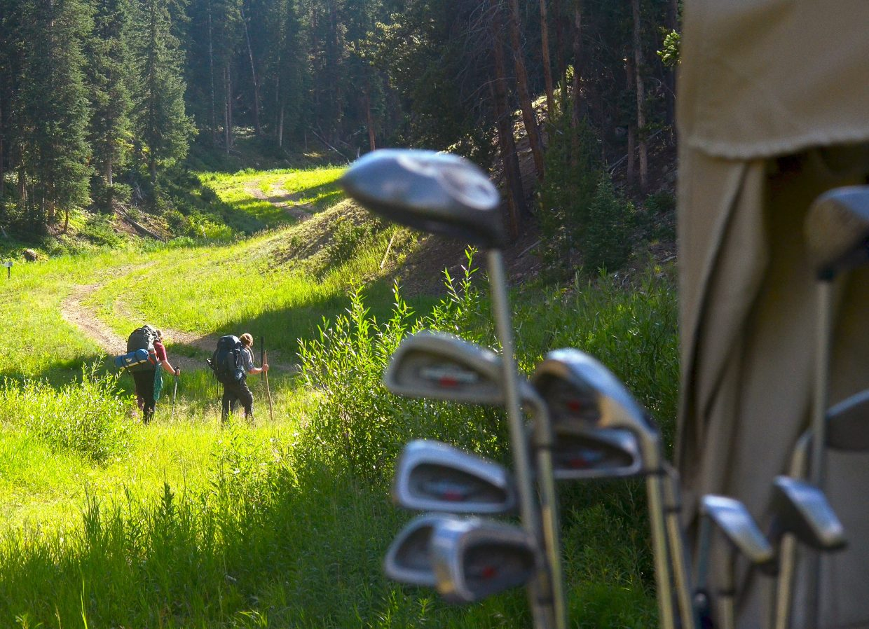 A duo of hikers pass by golf carts near the Hole 1 green at Copper Creek Golf Course at Copper Mountain. The course takes players on the slopes of east Copper Mountain before leveling out on the meadows surrounding the resort.
