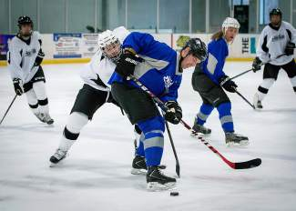 Players with the Beaver Run team (blue) and Vail-Summit Orthopaedics squad (white) jockey for the puck during the first round of the Summit Hockey Classic on April 1. Vail-Summit advanced to the championship game on April 2 and lost to Peak One Surgery Center, 7-2.