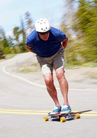 Longtime summit local Jim Bowden tucks into a straightaway near his home in Wildernest on a June afternoon. The New York native has been skateboarding and longboarding for nearly six decades, beginning in the '60s in California before he moved full-time to Summit County.