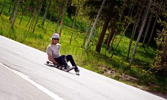 Summit local Slim Decamp slides through a corner on his longboard while bombing through the Wildernest neighborhood in early June. Decamp prefers the luge style, which he says gives the rider more control — and speed — than standing upright.