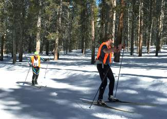 Tigers freshman skier Will Lewis (left) follows behind Nordic head coach Jonathan Mocatta during a race earlier in the season. Lewis is visually impaired (he's legally blind) and has finished every high school race this winter.