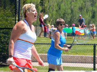 Loras Heck (left) of Kansas City reacts to a shot while playing doubles with Kathy Donahoe of Dallas during a drop-in clinic at the Breckenridge tennis courts. The clinics are a fun and laid-back way for players to learn new skills and meet new players.