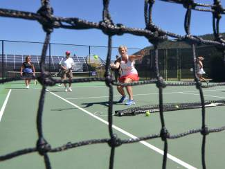 A group of adult tennis players rotates through the court for a volley drill during a drop-in clinic at the Breckenridge tennis courts.