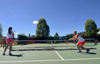 Two tennis players practice volleys with a ball machine during a drop-in clinic at the Breckenridge tennis courts in July.