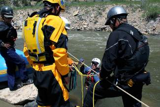 Allen Bond of Canon City meets with his rescue group after being transported across Clear Creek on a safety line during swift water rescue training in 2014. Rescue training is a must for raft guides and just about anyone who spends time on local waterways in the summer.