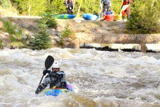 A kayaker weaves through the roiling Class IV rapids of Tenmile Creek as fellow paddlers watch from the bridge at Officer's Gulch. The creek is one of the most intense stretch in Summit County, but the season lasts less than four weeks in high seasons and sometimes as few as one or two days.